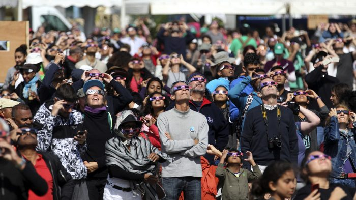"People look through eclipse viewing glasses, telescopes or photo cameras an annular solar eclipse, on September 1, 2016, in Saint-Louis, on the Indian Ocean island of La Reunion. Stargazers in south and central Africa were treated to a spectacular solar eclipse on September 1, 2016 when the Moon wanders into view to make the Sun appear as a ""ring of fire"", astronomers say. The phenomenon, known as an annular solar eclipse, happens when there is a near-perfect alignment of the Earth, Moon and Sun. But unlike a total eclipse, when the Sun is blacked out, sometimes the Moon is too far from Earth, and its apparent diameter too small, for complete coverage. / AFP PHOTO / Richard BOUHET"